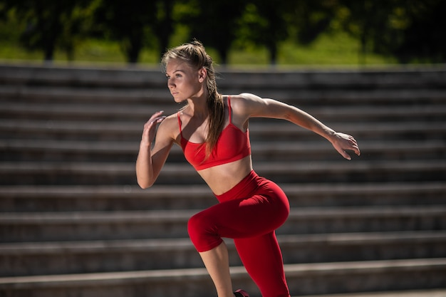 Young fitness woman running at the stadium