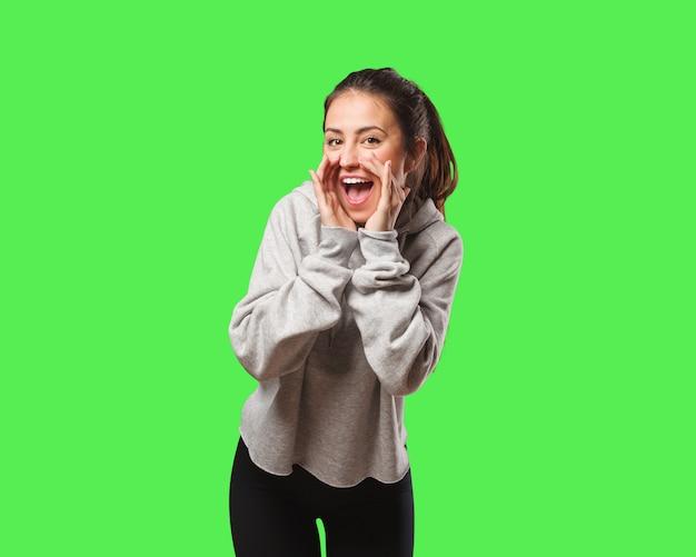 Молодая женщина фитнеса кричит что-то счастливое впереди