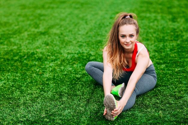 緑の草の上に座っている若いフィットネス女性。