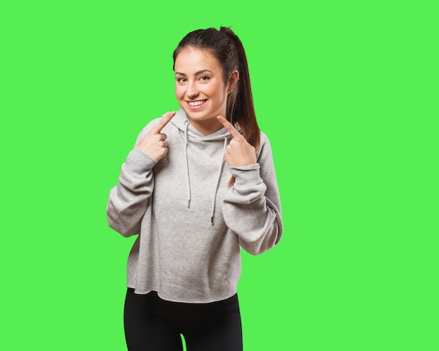 Young fitness woman smiles, pointing mouth