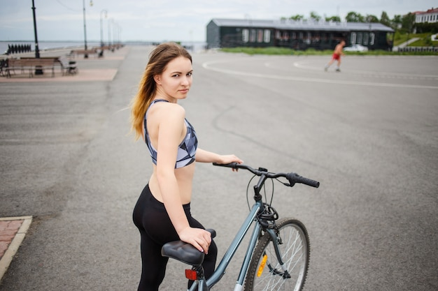Young fitness woman in sport wear posing outdoor with a bicycle