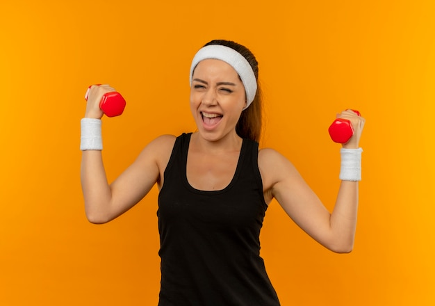 Young fitness woman in sportswear doing exercises using two dumbbells smiling cheerfully happy and excited standing over orange wall Free Photo