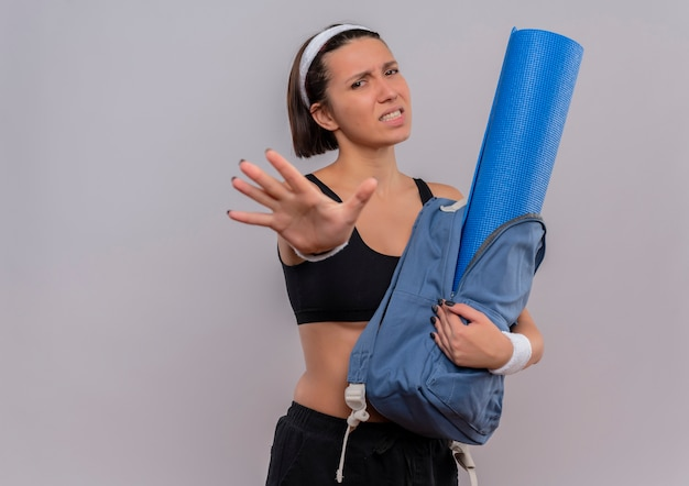 Young fitness woman in sportswear holding backpack with yoga mat doing stop sign with open hand with disgusted expression standing over white wall