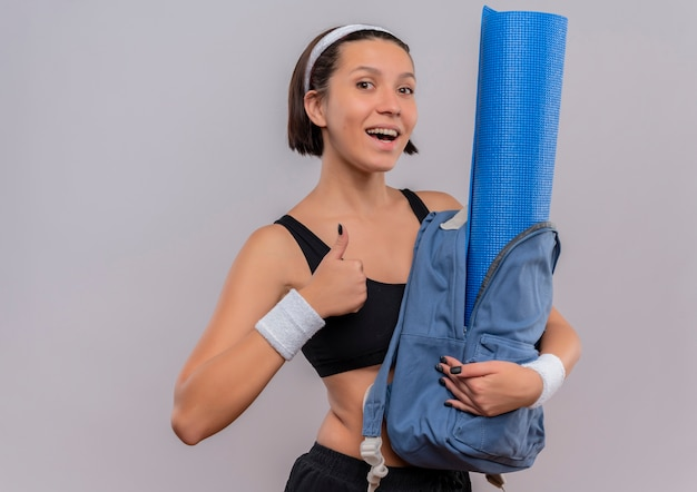 Young fitness woman in sportswear holding backpack with yoga mat with smile on face showing thumbs up standing over white wall