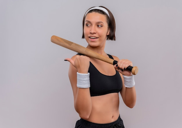 Young fitness woman in sportswear holding baseball bat looking aside with smile on face pointing back with thumb standing over white wall