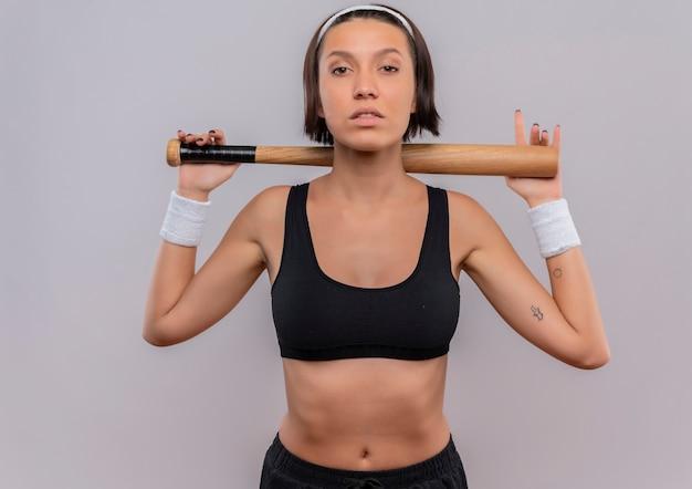 Giovane donna fitness in abiti sportivi tenendo la mazza da baseball sorridente fiducioso in piedi sopra il muro bianco
