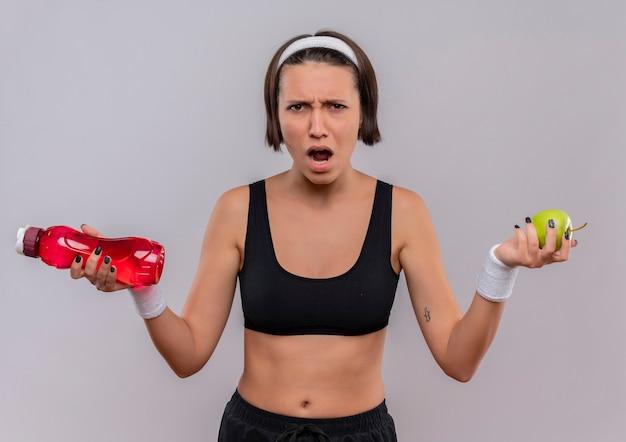 Giovane donna fitness in abiti sportivi tenendo la bottiglia di acqua e mela verde che grida con la faccia arrabbiata in piedi sopra il muro bianco
