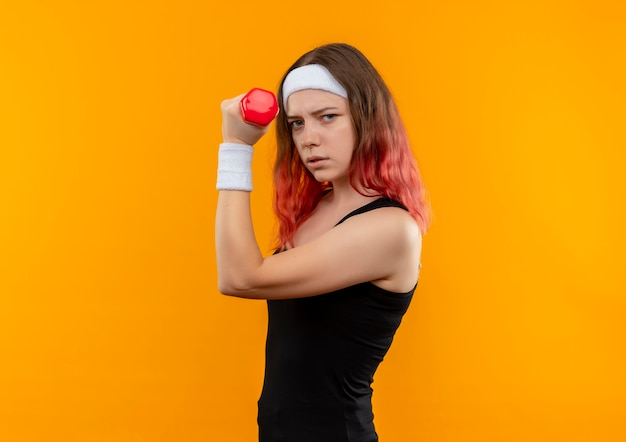 Young fitness woman in sportswear holding dumbbell doing power exercises with serious face standing over orange wall