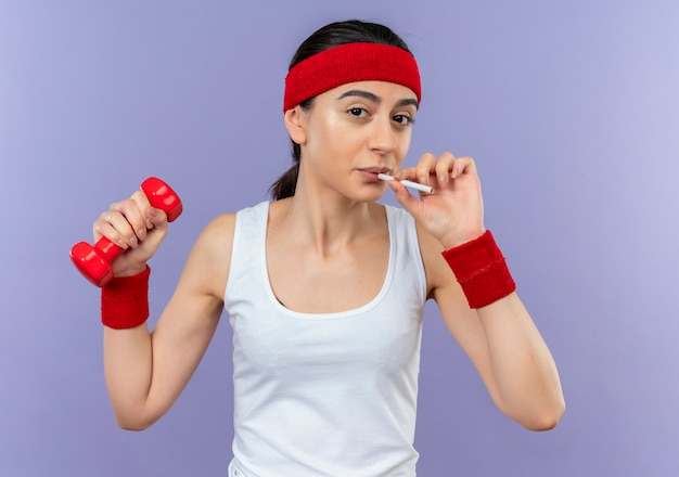 Young fitness woman in sportswear holding dumbbell with cigarette going to smoke standing over purple wall