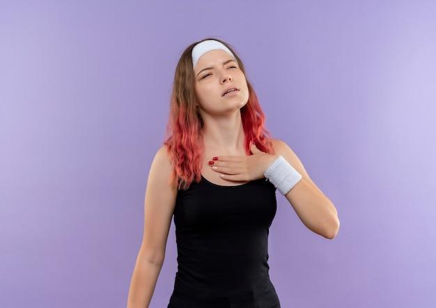 Giovane donna fitness in abiti sportivi tenendo la mano sul petto guardando stanco in piedi sopra la parete viola