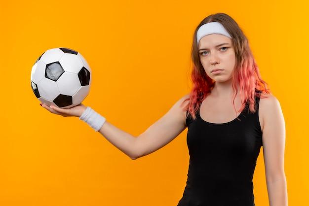 Giovane donna fitness in abiti sportivi tenendo il pallone da calcio in mano con la faccia seria in piedi sopra la parete arancione Foto Gratuite