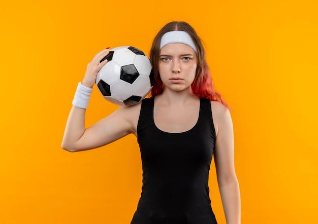 Giovane donna fitness in abiti sportivi tenendo il pallone da calcio in mano con la faccia seria in piedi sopra la parete arancione