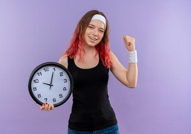 Giovane donna fitness in abbigliamento sportivo azienda orologio da parete pugno di serraggio felice ed uscito in piedi sopra la parete viola