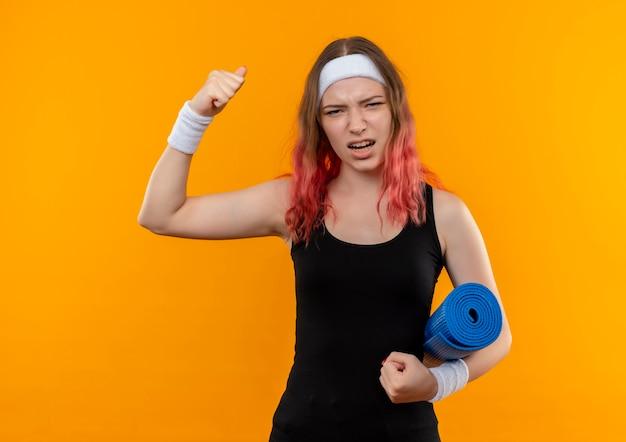 Giovane donna di forma fisica in abiti sportivi in possesso di stuoia di yoga alzando il pugno eccitato e felice in piedi sopra la parete arancione