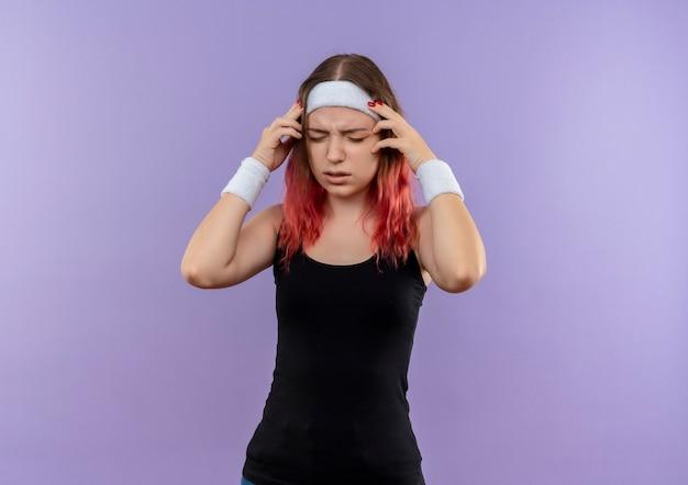 Giovane donna fitness in abiti sportivi alla ricerca di malessere toccando la testa soffre di mal di testa in piedi sopra la parete viola