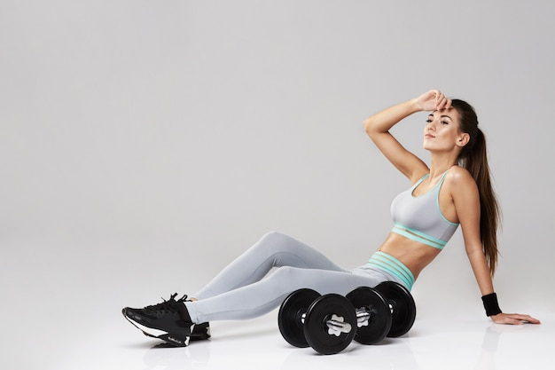 Young fitness woman in sportswear posing sitting with dumbbells on white.