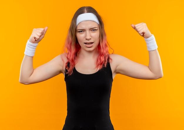 Giovane donna fitness in abiti sportivi alzando i pugni con espressione infastidita in piedi sopra la parete arancione