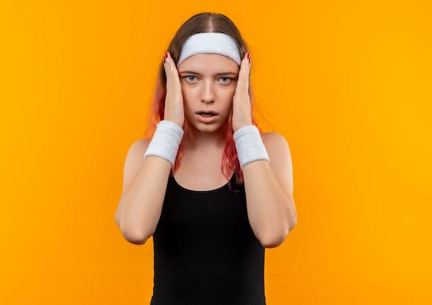 Giovane donna fitness in abiti sportivi scioccata toccando il viso con le braccia in piedi sopra la parete arancione