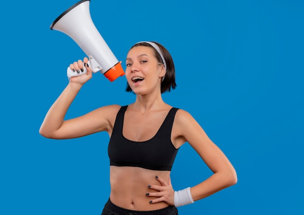Young fitness woman in sportswear shouting to megaphone looking happy and confident standing over blue wall