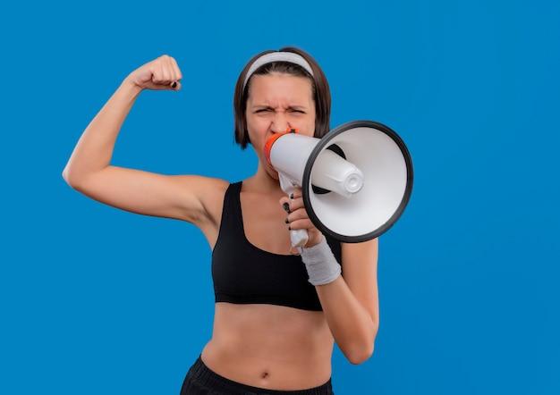 Giovane donna di forma fisica in abiti sportivi che grida al megafono con l'espressione aggressiva che alza il pugno, concetto del vincitore che sta sopra la parete blu