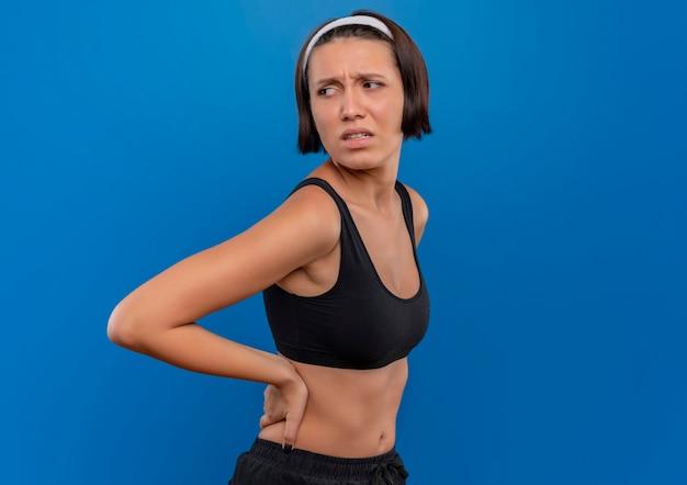 Giovane donna fitness in abiti sportivi toccando la schiena guardando da parte confuso e molto ansioso in piedi oltre la parete blu