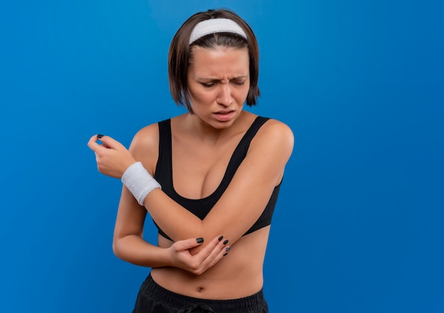 Giovane donna fitness in abiti sportivi che tocca il suo gomito avendo dolore in piedi sopra la parete blu