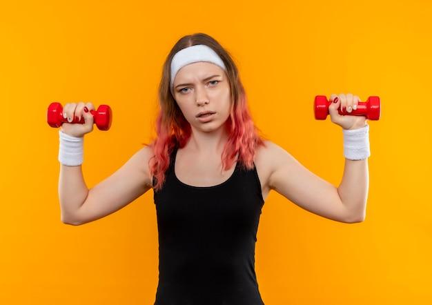 Giovane donna fitness in abiti sportivi utilizzando manubri facendo esercizi cercando fiducioso in piedi sopra la parete arancione