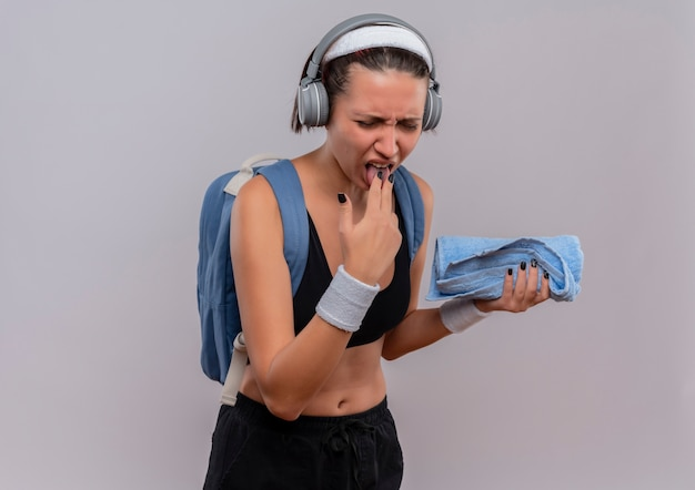 Young fitness woman in sportswear with backpack and headphones on head holding towel sticking out tongue with disgusted expression standing over white wall