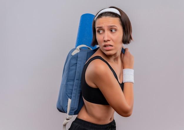 Giovane donna fitness in abiti sportivi con zaino e materassino yoga guardando indietro con espressione di paura in piedi sopra il muro bianco