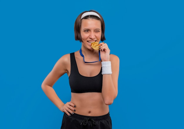 Young fitness woman in sportswear with gold medal around her neck biting medal smiling standing over blue wall
