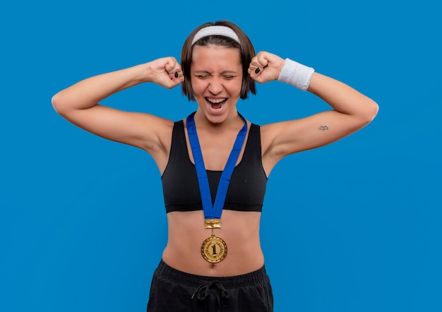 Young fitness woman in sportswear with gold medal around her neck clenching fists rejoicing her success standing over blue wall