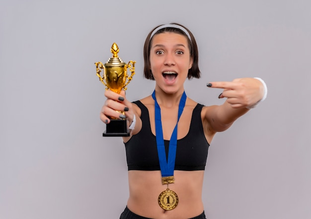 Young fitness woman in sportswear with gold medal around her neck holding her trophy pointing with finger to it happy and excited rejoicing her success standing over white wall