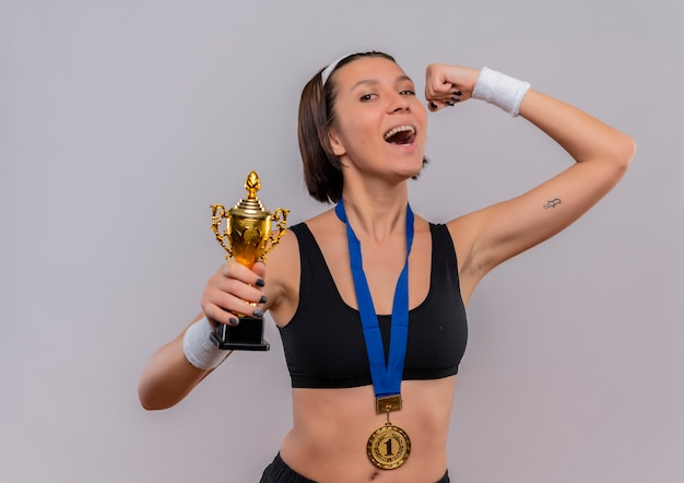 Young fitness woman in sportswear with gold medal around her neck holding her trophy raising fist happy and excited rejoicing her success standing over white wall