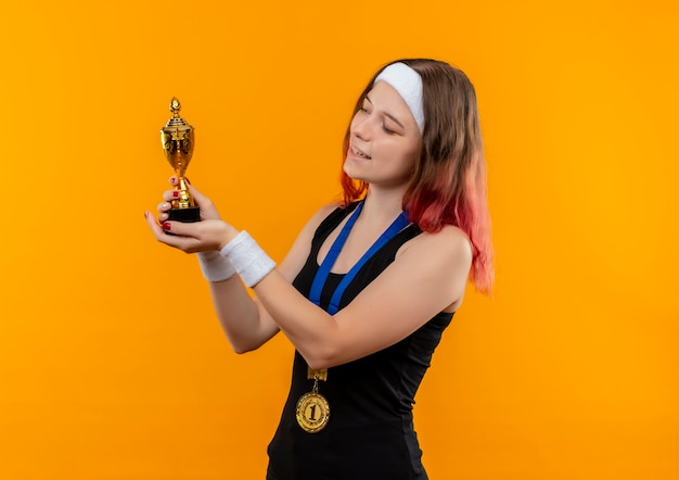Young fitness woman in sportswear with gold medal around her neck holding trophy looking at it smiling cheerfully standing over orange wall