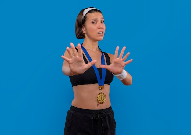 Young fitness woman in sportswear with gold medal around her neck making defense gesture with hands scared standing over blue wall