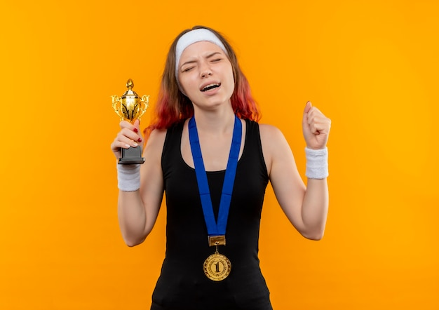Young fitness woman in sportswear with gold medal around her neck raising fists holding trophy with annoyed expression standing over orange wall