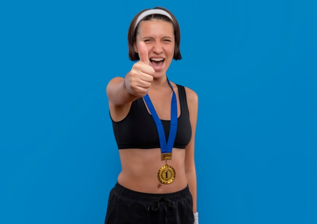 Young fitness woman in sportswear with gold medal around her neck showing thumbs up rejoicing her success happy and excited standing over blue wall