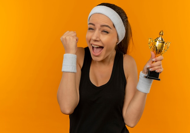 Young fitness woman in sportswear with headband clenching fist holding trophy happy and excited standing over orange wall