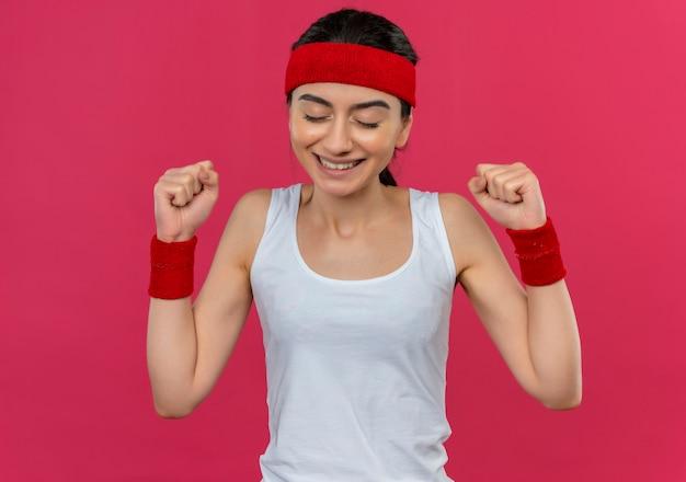 Giovane donna di forma fisica in abiti sportivi con la fascia che stringe i pugni felici ed eccitati che si rallegrano del suo successo in piedi sopra la parete rosa