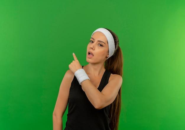 Giovane donna fitness in abiti sportivi con fascia confusa puntando il dito sul lato in piedi sopra la parete verde