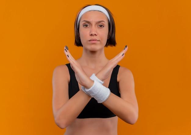 Giovane donna fitness in abiti sportivi con fascia incrocio le mani facendo gesto di difesa in piedi sopra la parete arancione