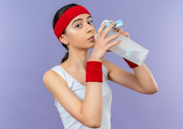 Young fitness woman in sportswear with headband drinking water looking tired standing over purple wall