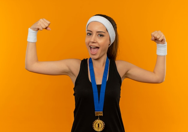 Young fitness woman in sportswear with headband and gold medal around her neck clenching fists