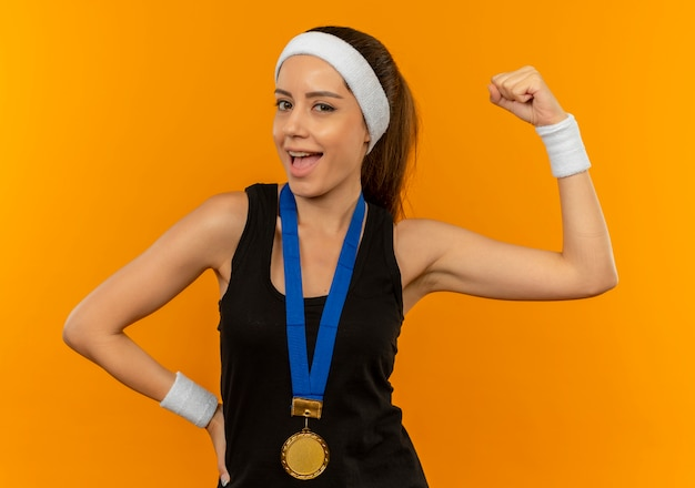 Young fitness woman in sportswear with headband and gold medal around her neck raising fist smiling happy and positive standing over orange wall
