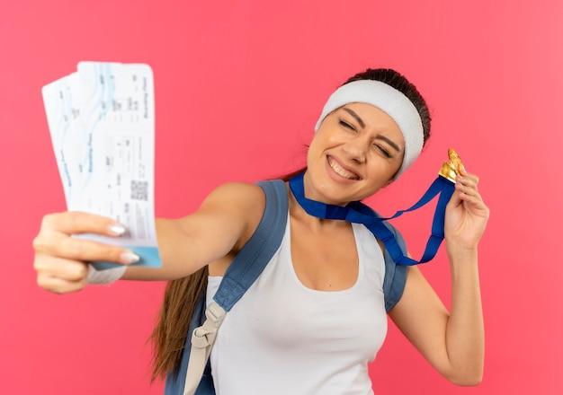 Giovane donna fitness in abbigliamento sportivo con fascia e medaglia d'oro al collo con zaino che mostra i biglietti aerei sorridendo allegramente in piedi sopra il muro rosa