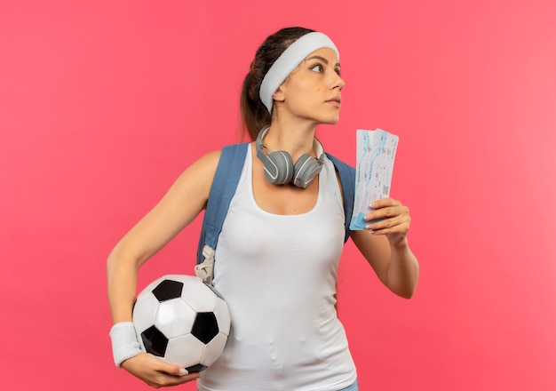 Young fitness woman in sportswear with headband and headphones around her neck holding air tickets and soccer ball looking aside with serious face standing over pink wall