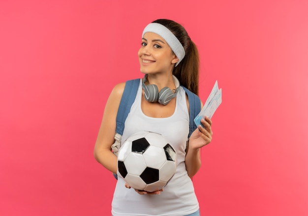 Young fitness woman in sportswear with headband and headphones around her neck holding air tickets and soccer ball looking aside with smile on face standing over pink wall