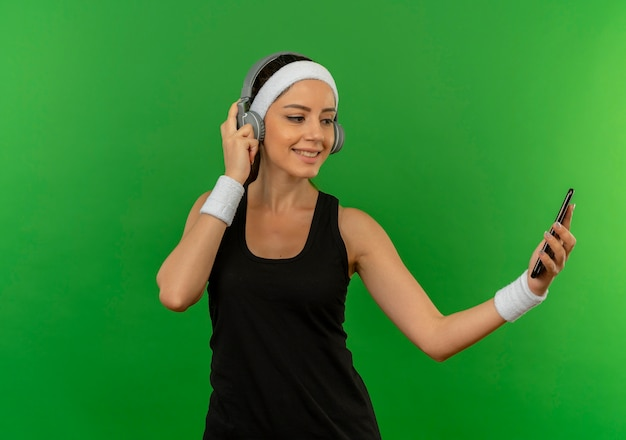 Young fitness woman in sportswear with headband and headphones looking at screen of her smartphone smiling confident standing over green wall