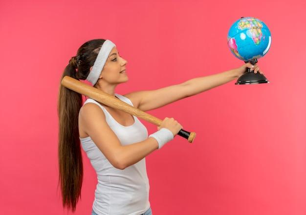 Giovane donna fitness in abiti sportivi con fascia tenendo una mazza e globo sorridente fiducioso in piedi sopra la parete rosa