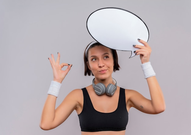 Young fitness woman in sportswear with headband holding blank speech bubble sign making meditation gesture with fingers feeling positive emotions smiling standing over white wall